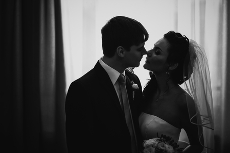 honeymoon suite: Black white photography beautiful young  couple standing near the window