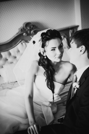 black and white photography: Black  white photography beautiful young couple sitting on the bed Stock Photo