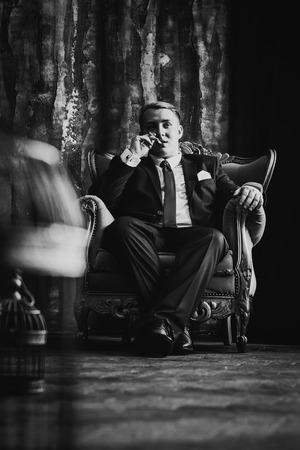 暗い背景に黒のクラシックなスーツを着た男の黒の白の写真肖像画。