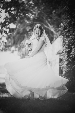 trees photography: Black white   photography stylish beautiful happy bride holding  bouquet of flowers on a background of trees in the summer park full length Stock Photo