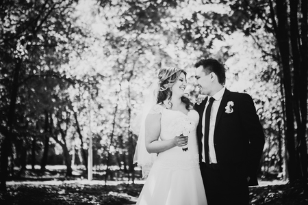 black and white photography: Black white photography happy couple bride and groom embracing they stand  in a forest