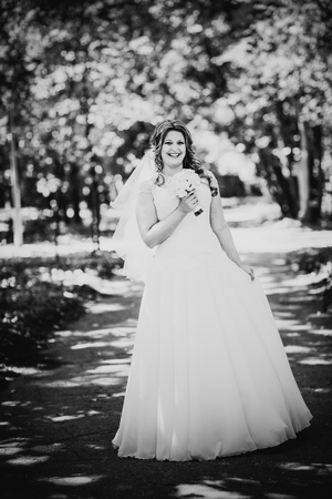 trees photography: Black white photography stylish beautiful happy bride holding   bouquet of  flowers on a background of trees in the summer park close-up