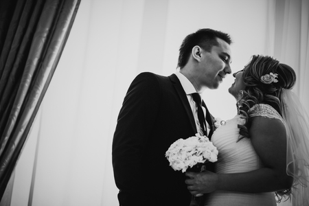 black and white photography: Black white photography  bride and groom posing in a hotel room on background windows