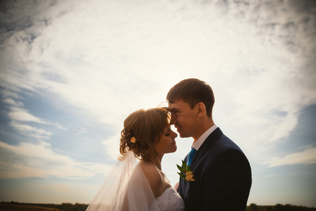 blue summer sky: young  bride and groom on the background sky Stock Photo