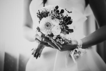 Zwart wit fotografie mooi huwelijksboeket van bloemen in handen de bruid
