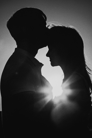 black and white photography: Black white photography romantic silhouette  couple standing and kissing on background summer meadow sunset Stock Photo