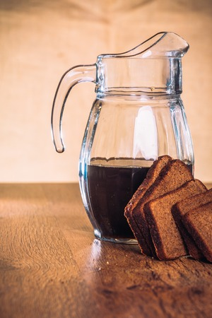 unbottled: Russian brew in jug  and loaf of rye flour on wooden background
