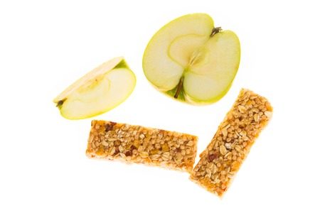 roughage: muesli bars with dried fruit on isolated background with  apple