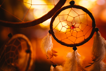 black and white photo of a dream catcher at sunset purple dark background.