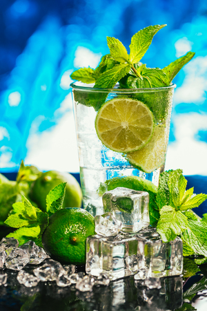 red straw: glass of mojito with lime and mint ice cube close-up with red straw on blue background.