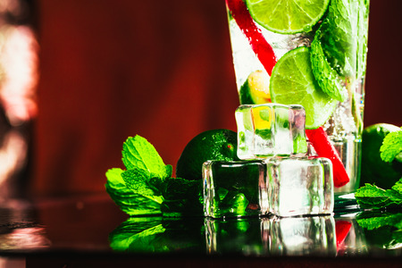 glass of mojito with lime and mint ice cube close-up with red straw.
