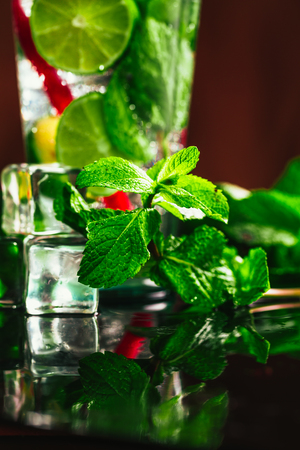 red straw: glass of mojito with lime and mint ice cube close-up with red straw.
