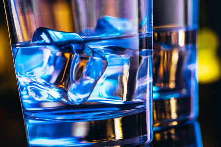 Two glasses of vodka with ice closeup.