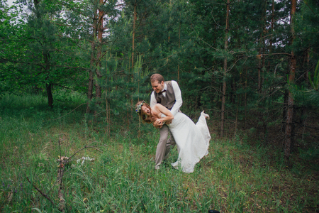 Bride and groom fooling around on the background of leaves and forest.