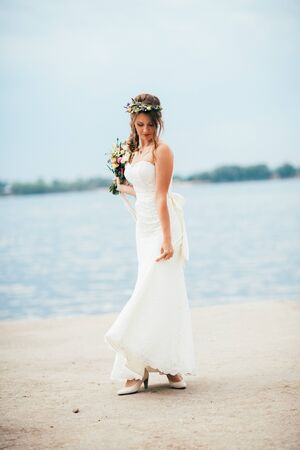 young bride with a bouquet of flowers standing on the background of the river.