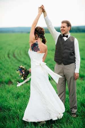 the bride and groom with a bouquet on the green field.