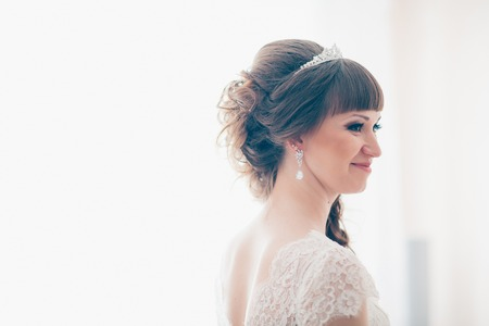 young bride smiling and standing near a window. Stock Photo
