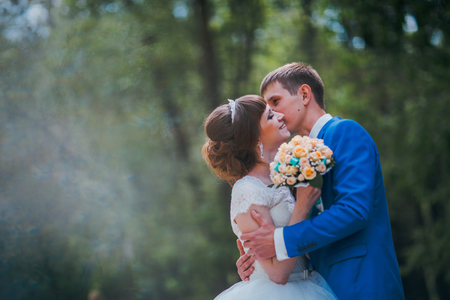 young bride and groom kissing on the background of the forest.