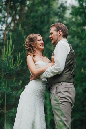 Bride and groom are embracing against the background forest.