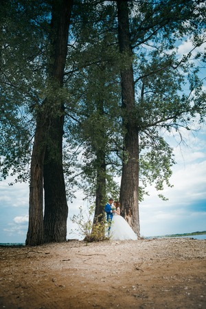 bride and groom standing and hugging on the background of trees.
