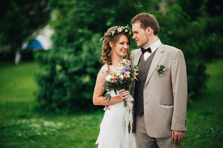 Young happy bride and groom on the background of greenery.