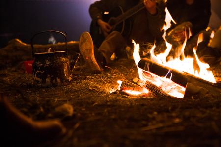 fogatas: hombre toca la guitarra y la mujer sobre el incendio en el fondo del cielo estrellado. Foto de archivo