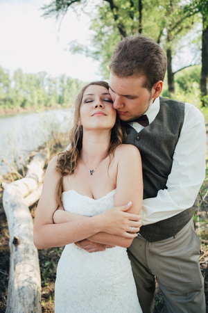bride and groom standing arm in arm against the background grass and lakes.