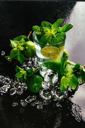 glass of mojito with lime and mint ice cube close-up with red straw on dark background. Stock Photo