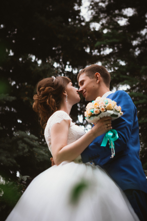 bride and groom kissing in the background of the nature.