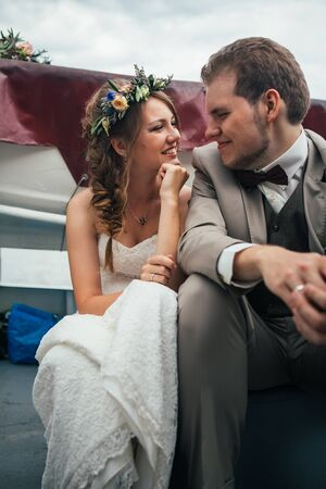 young happy bride and groom in a boat on the background of buildings. Stock Photo