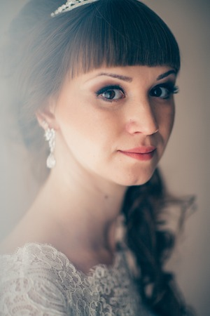 portrait of a young bride smiling and standing near a window.