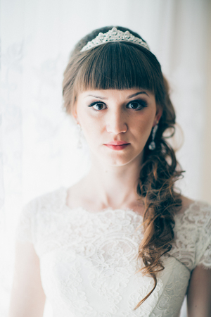 portrait of a young bride standing near a window. Stock Photo