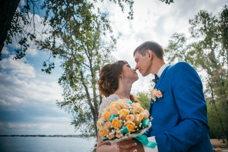 bride and groom standing and kissing in the background of the nature. Stock Photo