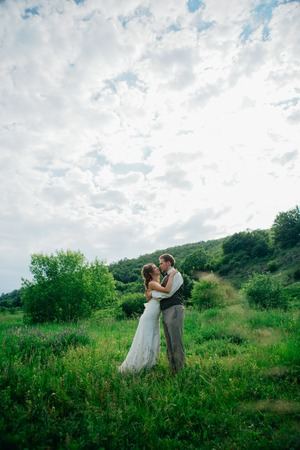 the bride and groom with a bouquet in the grass against the background mountain landscape.