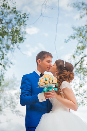 bride and groom kissing on the background of trees. Stock Photo