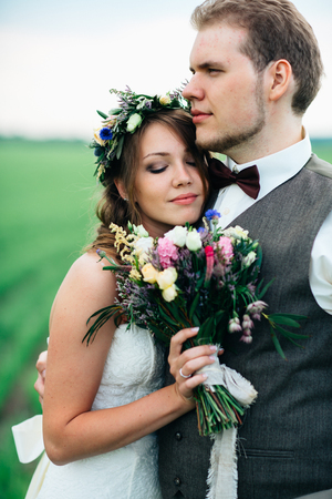 portrait of the bride and groom with a bouquet on the green field.
