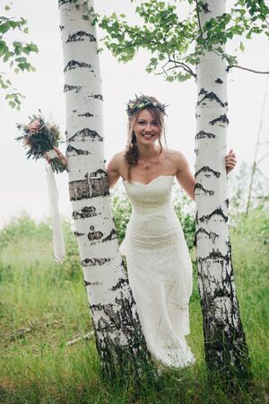 portrait of a bride on a background of leaves and forest.