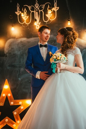 bride and groom in the interior of the studio are on the background wall. Stock Photo