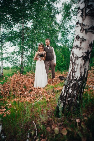 Bride and groom hugging on the background of leaves and forest
