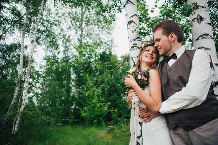 portrait of a bride and groom embrace on a background of leaves and forest.