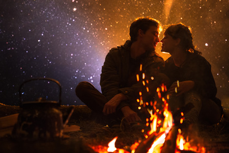 man plays guitar and woman about the fire on the background of the starry sky.