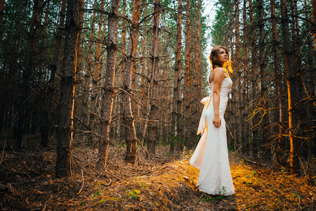 Bride with a tattoo on a background of leaves and forest backlight.