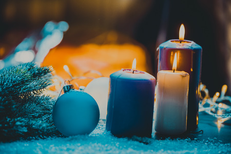 advent season: christmas decoration with christmas bauble and candle for advent season four candles burning.