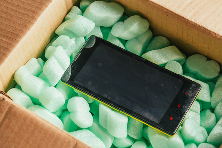 padding: parcel of online shop, phone in a cardboard box on a green polystyrene. Stock Photo