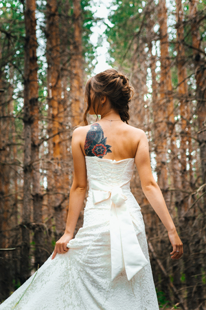desire: Bride with a tattoo on a background of leaves and forest backlight.