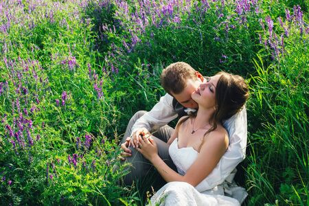 portrait of the bride and groom resting on a lavender background. Stock Photo