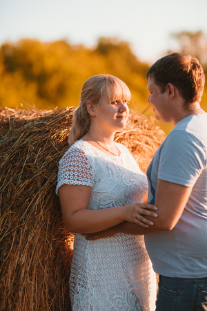 love story man and woman on the background of haystacks and sun. Stock Photo