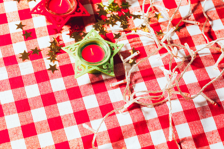 candle on red checkered tablecloths and garland.