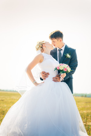 the bride and groom on the background of field. Stock Photo