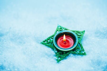 res: red candle in green candlestick star on the snow.